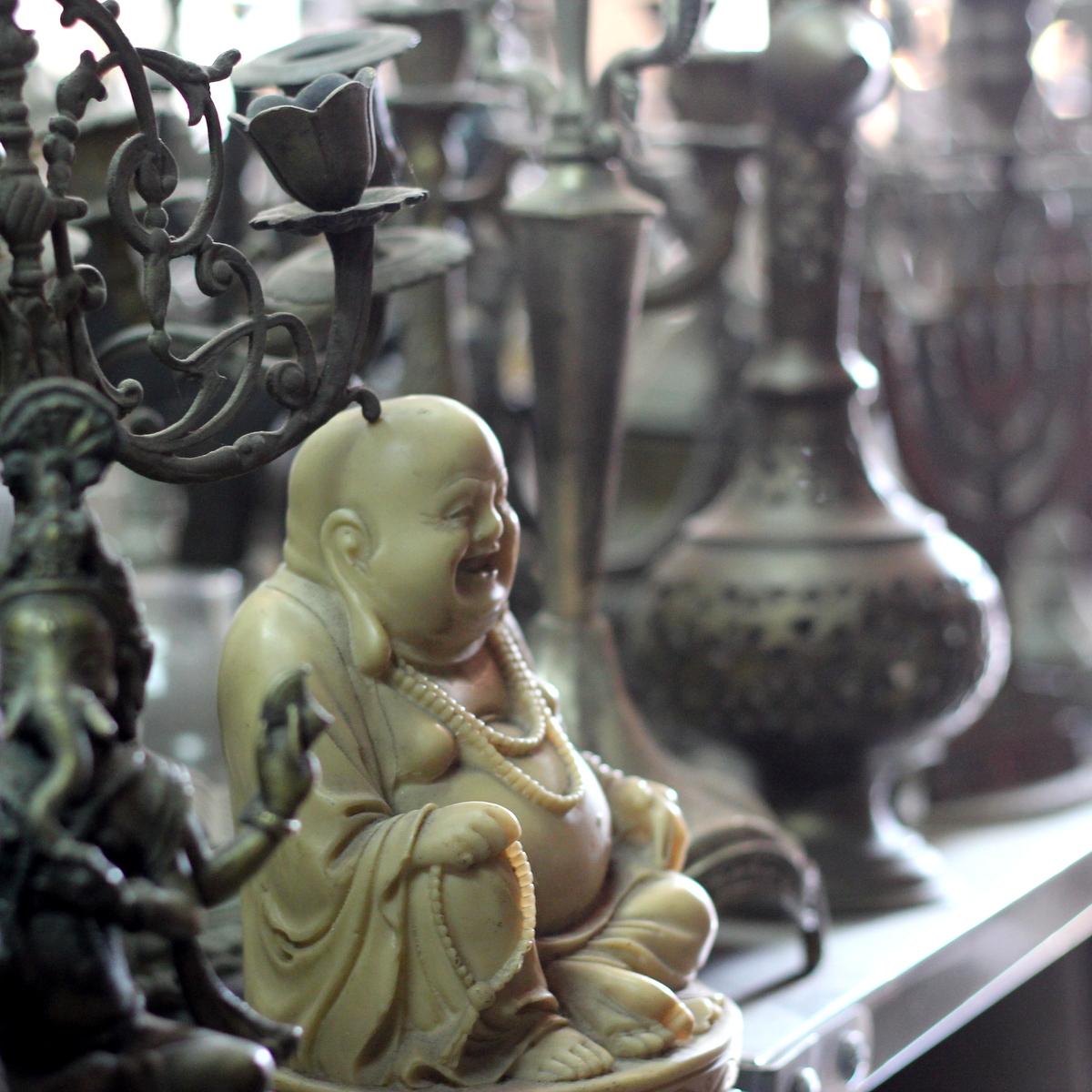 חנות אפלולית של חנוכיות וכלי פליז עם בודהה יחיד ומיוחד זו סיבה לאהוב שווקי פשפשים